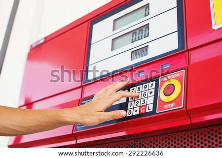 hand pressing buttons on a fuel refill machine on gas station - stock photo