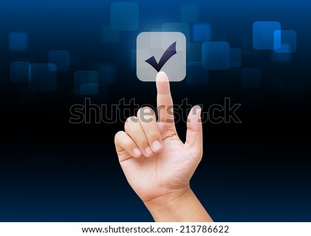 Hand pressing check mark buttons with technology background  - stock photo
