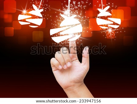 Hand pressing Christmas ball buttons on holiday background - stock photo
