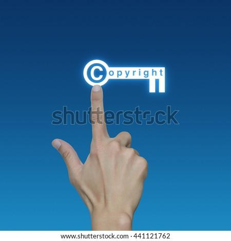 Hand pressing copyright key icon on blue background, Copyright and patents concept - stock photo