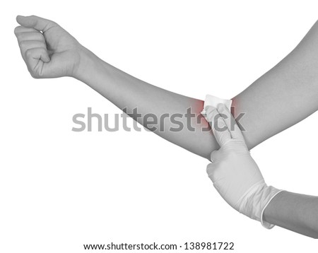 Hand pressing gauze on arm after administering an injection. Colour enhanced skin to emphasize problematic part. - stock photo