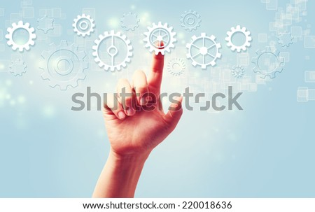 Hand pressing gear icons over light blue background - stock photo