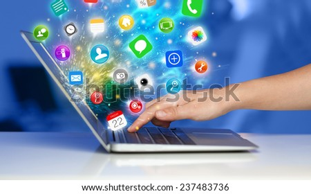 Hand pressing modern laptop with mobile app icons and symbols comming out - stock photo