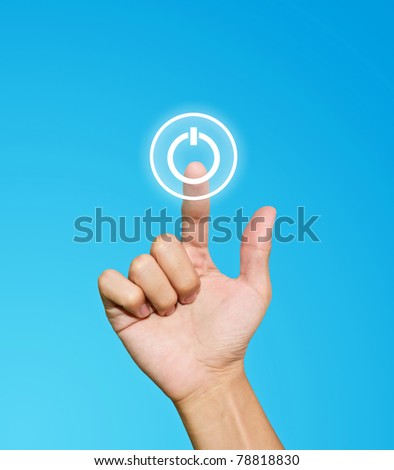 Hand pressing power button on blue background - stock photo