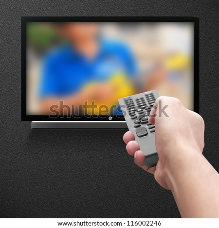 Hand pressing remote control - stock photo