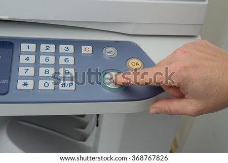 Hand pressing Start button on copy machine isolated