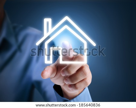 Hand pressing the house icon - stock photo