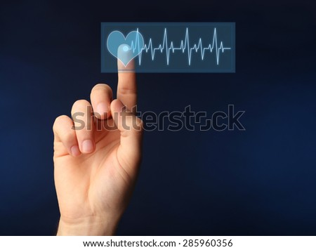Hand pressing virtual button with heart diagram