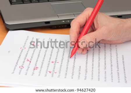 Hand Proofreading a Manuscript beside Laptop - stock photo