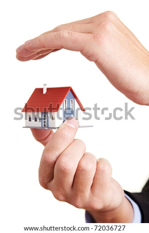 Hand protecting a small miniature house with a roof - stock photo