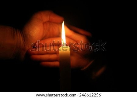 hand protects the flame from a candle burning on a dark background