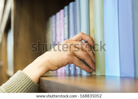Hand pulling a book off the shelf. Blue colors books - stock photo