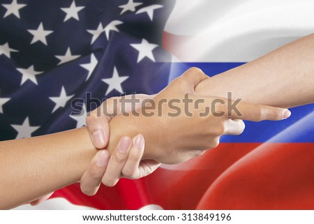 Hand pulling a person's hand for helping and rescuing in front of the american and russian flags