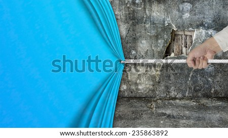 hand pulling open blank blue curtain covered old broken wall ruins background - stock photo