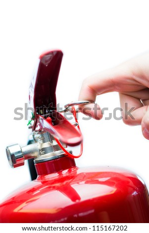 Hand pulling safety pin from red fire extinguisher - stock photo