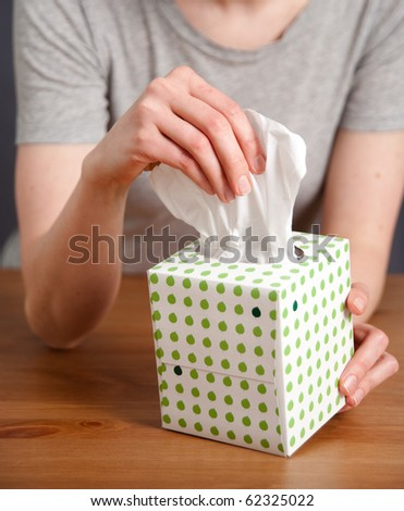 Hand Pulling Tissue out of Box - stock photo