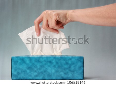 hand pulling white tissue from blue box