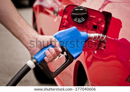 Hand Pumping Gas Into Red Car - stock photo