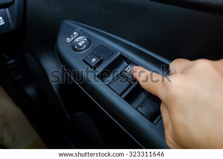 Hand push button mirror in car / Hand asian push button mirror in car - stock photo