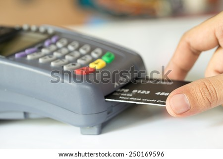 Hand Push Credit Card Into A Credit Card Machine : Selective Focus - stock photo