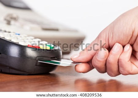 Hand push credit card Into a credit card machine.Studio shot. Selective Focus.