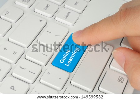Hand pushing blue online learning button on keyboard