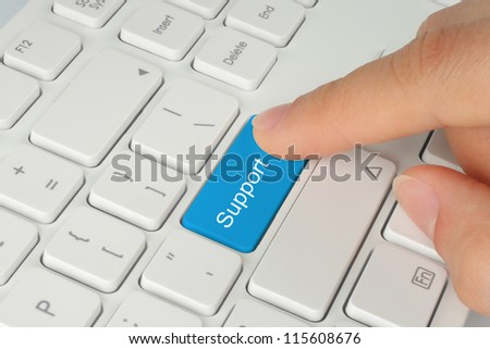Hand pushing blue support keyboard button - stock photo
