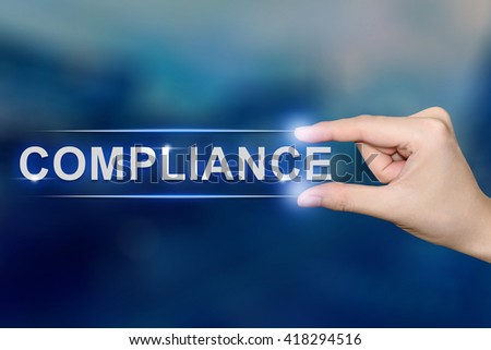 hand pushing compliance button on blurred blue background - stock photo