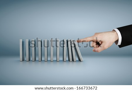 Hand pushing dominoes concept isolated on blue background - stock photo