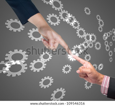 Hand pushing gear button on a touch screen interface - stock photo