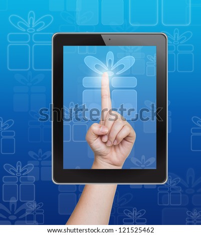 Hand pushing gift box button of tablet on a touch screen - stock photo