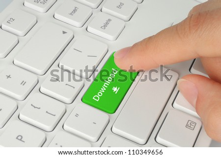 Hand pushing green download keyboard button - stock photo
