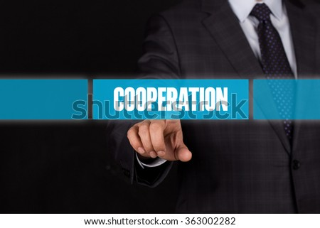 Hand pushing on a touch screen interface-COOPERATION button - stock photo