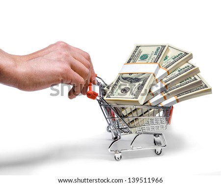 hand pushing shopping cart full of stacks of dollar bills isolated on white  - stock photo