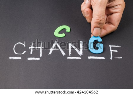 Hand put a wood letter into guess word game for Change concept - stock photo