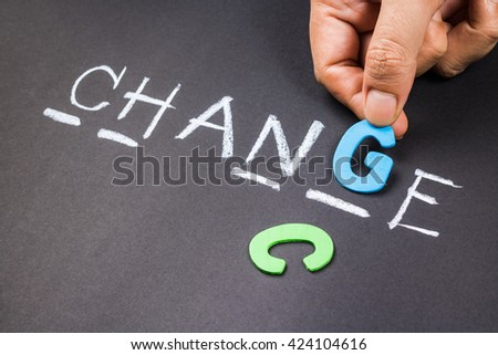 Hand put a wood letter into guess word game for Change concept