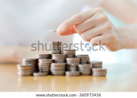 Hand put coins to stack of coins - stock photo