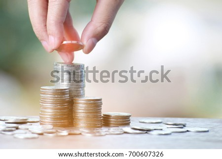 Hand put coins to stack of coins,Savings money and income or Investment Ideas and Financial Management for the Future