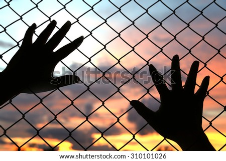 hand put on the chain link fence on an evening sunset with depth of field, out of focus sunset. Sunset with amazing sunset background. Industrial sunset.Silhouette on sunset sky