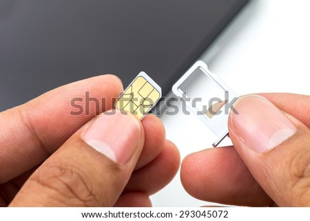 Hand put sim card to the sim card tray - stock photo