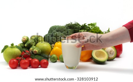 hand puts a glass with a cocktail on a background of vegetables and herbs - stock photo