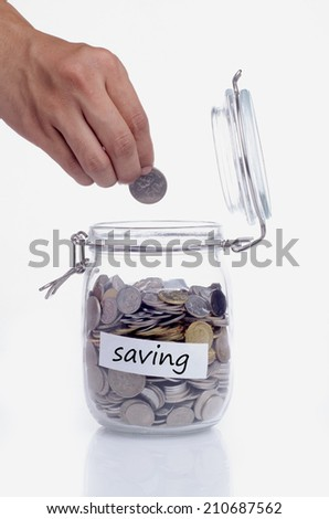 Hand putting a coin into glass jars with 'saving' text - stock photo