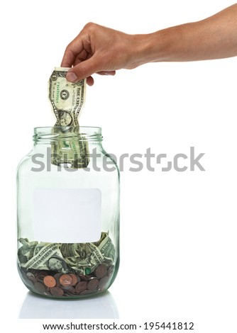 hand putting a dollar bill in a savings jar with a white label  - stock photo