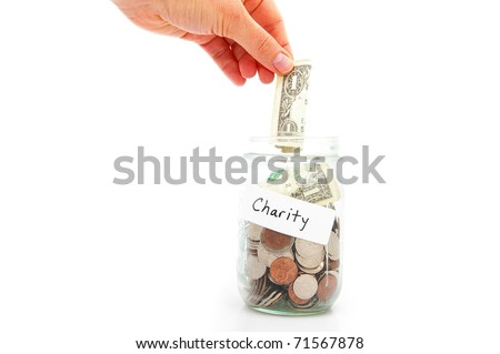hand putting a dollar into a jar - charity donation - stock photo