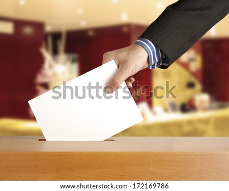 Hand putting a voting ballot in a slot of box - stock photo