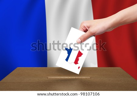 Hand putting a voting ballot to wooden box on Flag of France - stock photo
