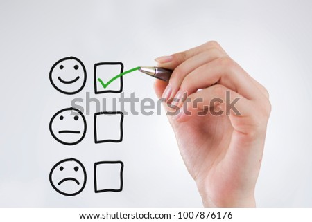 Hand putting check mark with green marker on customer service evaluation form
