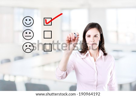 Hand putting check mark with red marker on customer service evaluation form. Office background. - stock photo