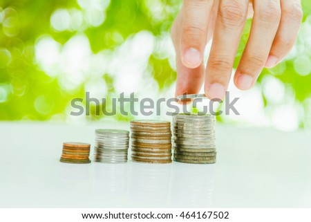 Hand putting coin on coins stack with copy space and sunlight, savings, finance , business investment growth concept.
