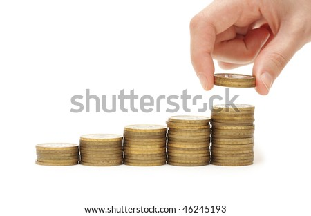 Hand putting coin to money staircase isolated on white background - stock photo